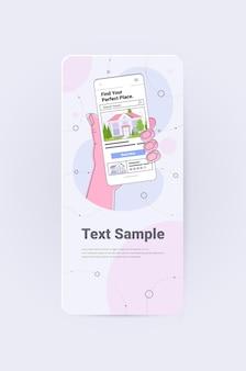 Menselijke hand met behulp van mobiele app voor het zoeken naar huizen voor het huren of kopen van online vastgoedbeheerconcept verticale kopieerruimte
