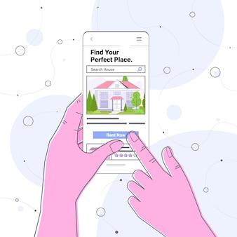 Menselijke hand met behulp van mobiele app voor het zoeken naar huizen voor het huren of kopen van online vastgoedbeheerconcept