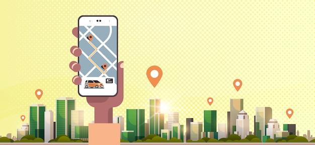 Menselijke hand met behulp van online bestellen taxi autodelen mobiele applicatie concept vervoer autodelen service app smartphone scherm met gps kaart moderne stadsgezicht achtergrond horizontaal