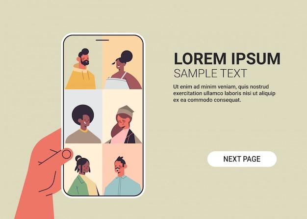 Menselijke hand met behulp van smartphone chatten met mix race vrienden tijdens videogesprek