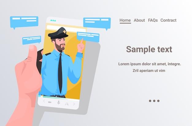 Menselijke hand met behulp van smartphone chatten met politieagent tijdens videogesprek
