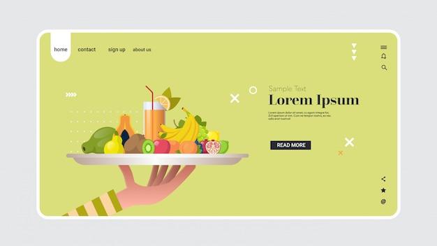 Menselijke hand met glas met sinaasappelsap gezonde sappige vitamine drinkt zoete tropische vruchten samenstelling in witte plaat veganistisch eten concept horizontale kopie ruimte