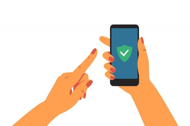 Menselijke hand met mobiele telefoon met groen schild op het scherm.