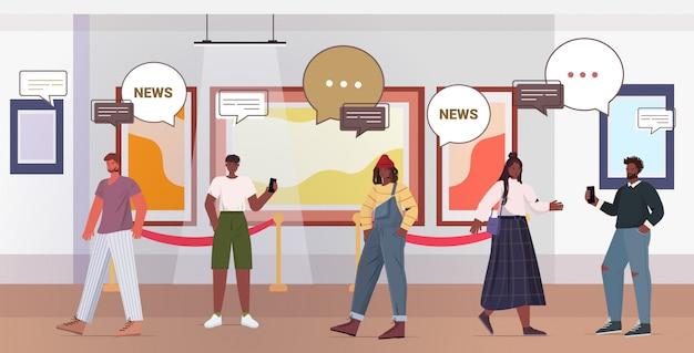 Mensen bespreken dagelijks nieuws tijdens bijeenkomst in kunstgalerie chat bubble communicatieconcept mix race bezoekers bekijken exposities in museum volledige lengte horizontale afbeelding