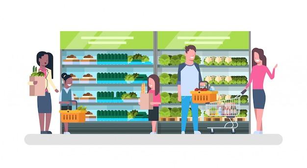 Mensen die bij supermarkt en het kopen producten winkelen, planken bij het concept van het kruidenierswinkelconsumentisme