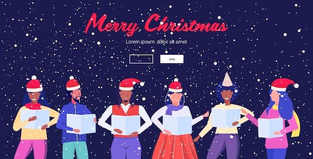 Mensen die bladboeken houden die prestaties geven vrolijk kerstfeest gelukkig nieuwjaar vakantie viering concept mannen vrouwen staan samen bestemmingspagina