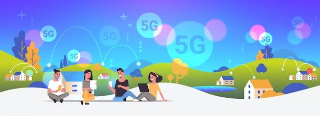 Mensen die digitale apparaten gebruiken 5g online draadloze systeemverbinding internet communicatieconcept mannen vrouwen zitten buiten platteland achtergrond volledige lengte horizontaal