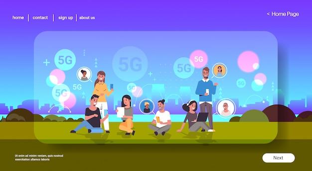 Mensen die digitale apparaten gebruiken sociale netwerkcommunicatie 5g online draadloos systeem verbinding concept mix race mannen vrouwen chatten zomer park stadsgezicht achtergrond volledige lengte horizontaal