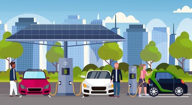 Mensen die elektrische auto's opladen bij elektrisch laadstation hernieuwbaar milieuvriendelijk voertuig schoon vervoer milieu zorgconcept moderne stadsgezicht achtergrond volledige lengte