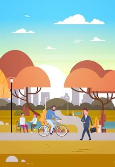 Mensen die in mooi de herfst stedelijk park ontspannen die berijdende fiets en het communiceren lopen