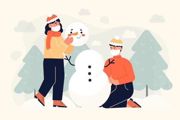 Mensen die samen een sneeuwpop maken terwijl ze gezichtsmaskers dragen