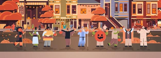 Mensen die verschillende monsterskostuums dragen die in stadstrucs lopen en happy halloween-feestviering concept stadsstraat gebouwen stadsgezicht behandelen
