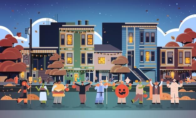 Mensen die verschillende monsterskostuums dragen die in stadstrucs lopen en het gelukkige halloween-concept van de partijviering behandelen stadsstraat gebouwen exterieur stadsgezicht