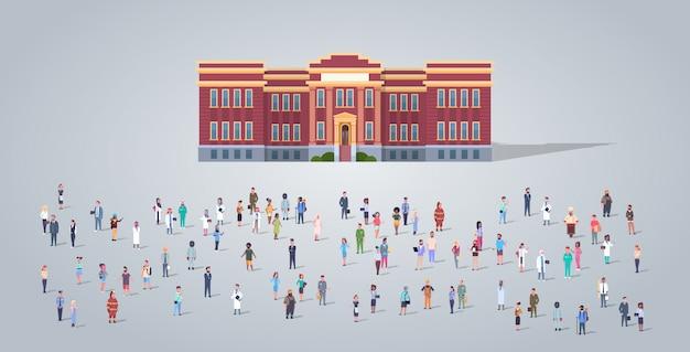 Mensen groeperen voor schoolgebouw verschillende bezetting werknemers mix race werknemers menigte onderwijs concept horizontale volledige lengte plat