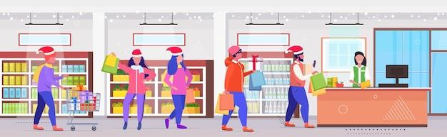 Mensen in santa hoeden met boodschappentassen staande lijn wachtrij bij kassa met vrouwelijke kassier kerstvakantie viering concept moderne winkel interieur