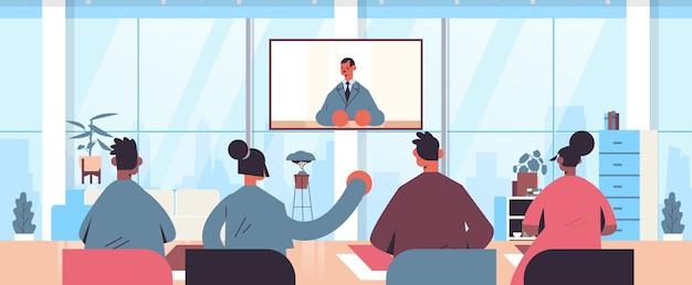 Mensen kijken naar online video-overleg met mannelijke arts op tv-scherm gezondheidszorg telegeneeskunde medisch advies concept