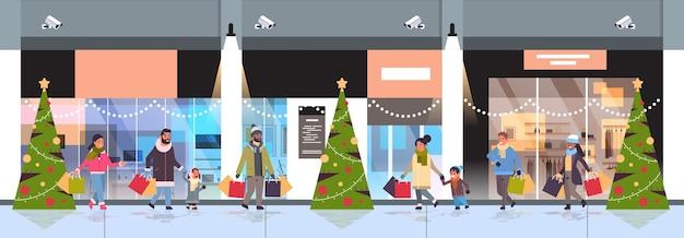 Mensen lopen met kleurrijke papieren zakken vrolijk kerstfeest gelukkig nieuwjaar winkelconcept ouders met kinderen die aankopen houden moderne winkelcentrum exterieur banner