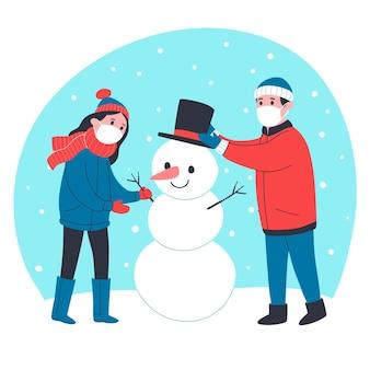 Mensen maken samen een sneeuwpop terwijl ze medische maskers dragen