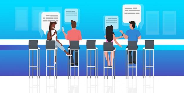 Mensen met behulp van chatten app zitten aan balie sociaal netwerk toespraak praatje bubble communicatieconcept