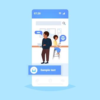Mensen met behulp van mobiele app chat bubble sociale media communicatieconcept afro-amerikaanse café bezoekers koffie drinken online toespraak gesprek volledige lengte smartphone scherm