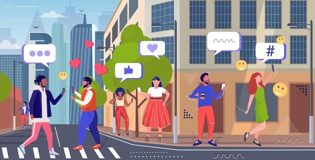 Mensen met behulp van online mobiele app sociale media netwerk chat bubble communicatie concept mix race mannen vrouwen lopen op straat stadsgezicht achtergrond schets volledige lengte horizontaal
