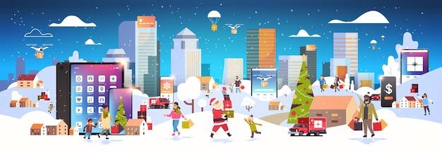Mensen met boodschappentassen die buiten lopen met behulp van online mobiele app-tekens die zich voorbereiden op kerstmis nieuwjaarsvakantie winter stadsgezicht banner