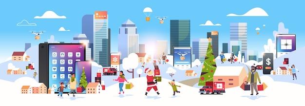 Mensen met boodschappentassen die buiten lopen met behulp van online mobiele app-tekens die zich voorbereiden op kerstmis, nieuwjaarsvakantie, winterlandschap