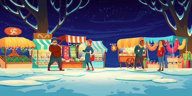 Mensen op kerstmarkt met marktkraampjes met snoepjes, kerstmutsen, cakes en peperkoek.