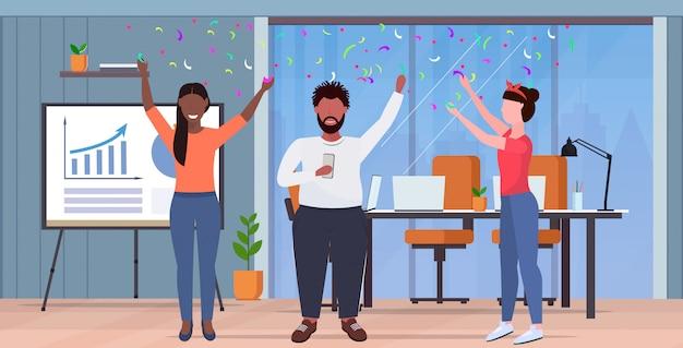 Mensen uit het bedrijfsleven verhogen armen collega's hebben partij confetti mix collega's vieren evenement concept modern kantoor interieur volledige lengte horizontaal