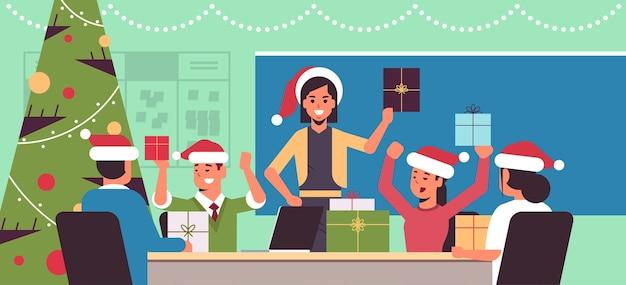 Mensen uit het bedrijfsleven vieren vrolijk kerstfeest en ondernemers dragen santa hoeden bedrijf geschenk huidige dozen wintervakantie concept moderne kantoor interieur plat