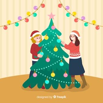 Mensen versieren kerstboom met bollen