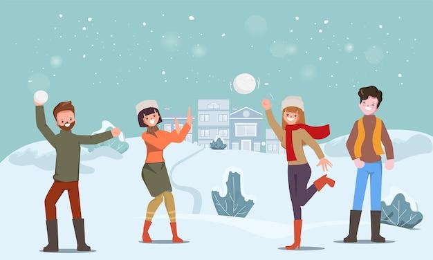 Mensen vieren sneeuwballen gooien op kerstmis in de wintervakantie.
