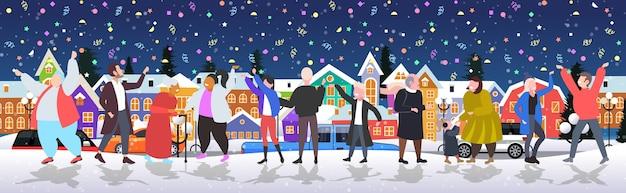 Mensen vieren vrolijk kerstfeest gelukkig nieuwjaar wintervakantie concept mannen vrouwen staan samen in de buurt van dennenboom met confetti party stadsgezicht