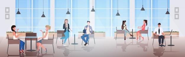 Mensen zitten aan cafe tafels bespreken tijdens vergadering modern in restaurant