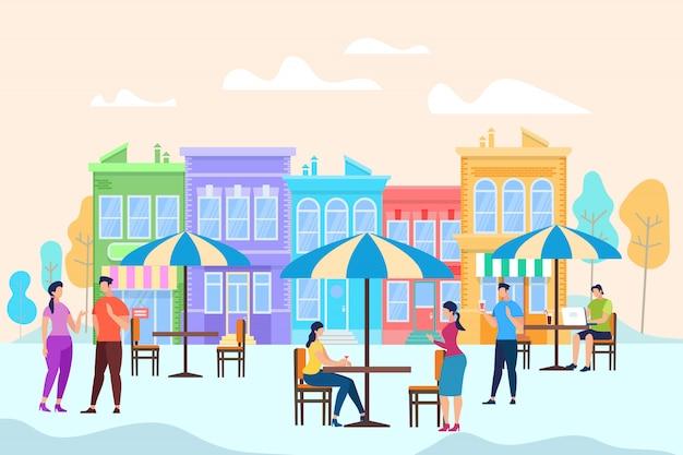 Mensen zitten en ontspannen aan tafels in open air cafe