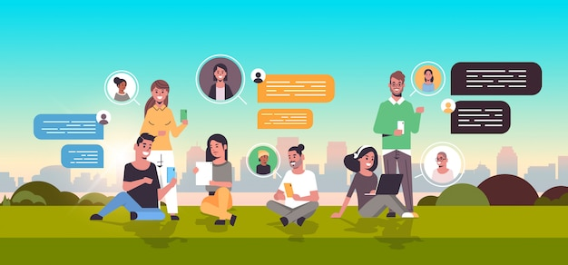 Mensen zitten op gras met behulp van chatten app op digitale apparaten sociaal netwerk chat bubble communicatieconcept