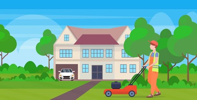Mensentuinman in eenvormig scherp gras met grasmaaimachine het tuinieren van het het plattelandshuisjeconcept van het concept modern plattelandshuisje volledige horizontale vlak lengte als achtergrond