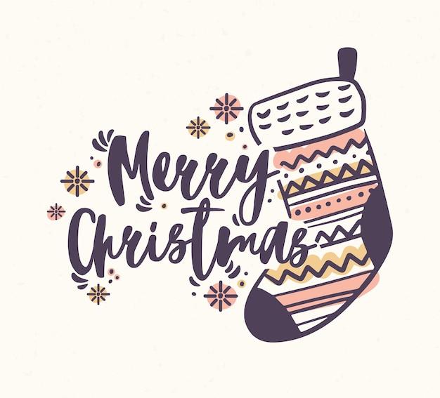 Merry christmas belettering handgeschreven met elegant kalligrafisch schrift en versierd met gebreide kous of sok en sneeuwvlokken