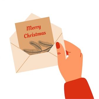 Merry christmas illustratie. een menselijke hand houdt een envelop met een wenskaart. vector
