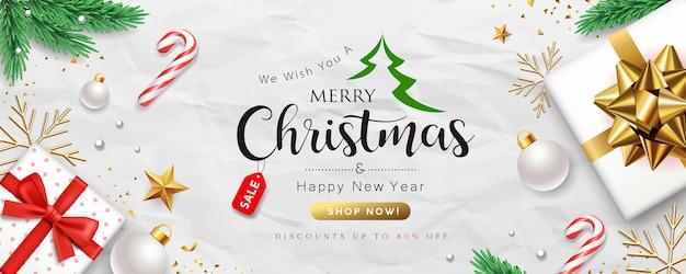 Merry christmas-verkoop, geschenkdooscollecties met kerstpersoneel, pijnboombladeren en gouden linten banner conceptontwerp op verfrommeld wit papier achtergrond