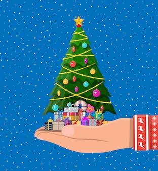 Met de hand versierde kerstboom en giftdozen Premium Vector