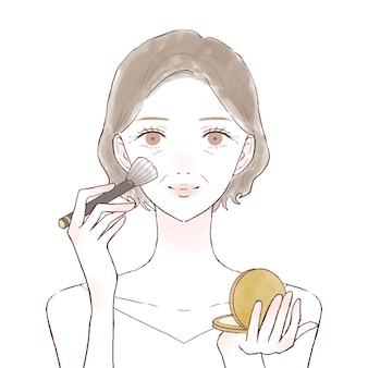 Middelbare oude vrouw die poederachtige foundation toepast om met make-upborstel onder ogen te zien. op een witte achtergrond.