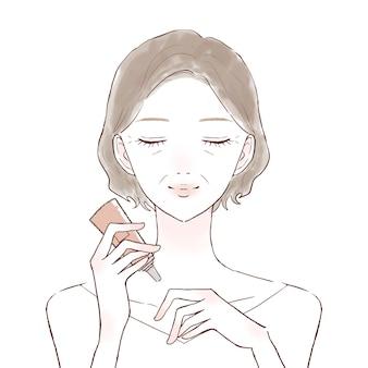 Middelbare oude vrouw die vochtinbrengende crème in haar hand neemt. op een witte achtergrond.