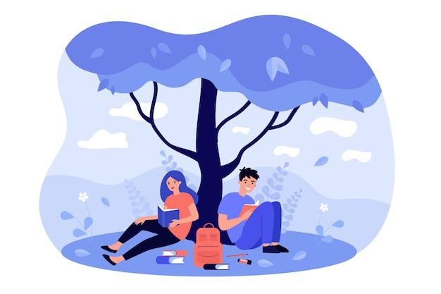 Middelbare scholieren zitten op gazon bij boom, boek lezen, huiswerk doen, samen studeren.