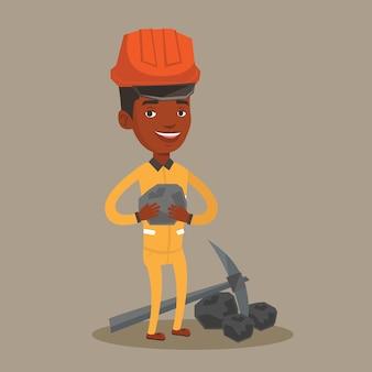 Mijnwerker die steenkool in handen houdt.