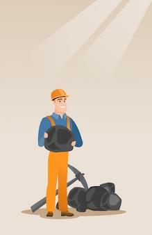 Mijnwerker die steenkool in handen houdt