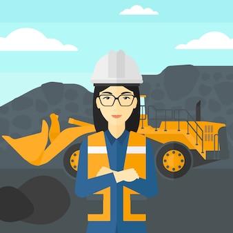 Mijnwerker met mijnbouwapparatuur op achtergrond.