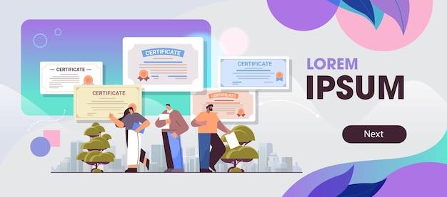 Mix race afgestudeerde ondernemers met certificaten gelukkige afgestudeerden vieren academisch diploma graad bedrijfsonderwijs concept horizontale volledige lengte kopie ruimte
