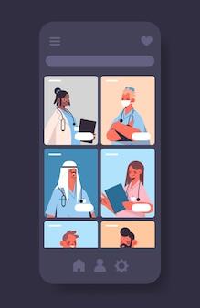 Mix race artsen in mobiele medische applicatie online overleg gezondheidszorg geneeskunde concept smartphone scherm verticaal