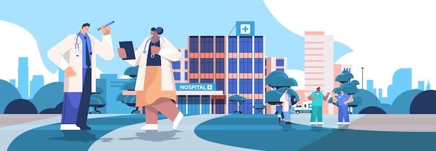 Mix race-artsen in uniform bespreken tijdens het ontmoeten van nette moderne ziekenhuisgebouw geneeskunde voor de gezondheidszorg